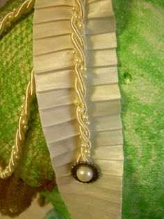 This is a hair band of pleated ivory satin, ivory and pearl roping and a blond hair net