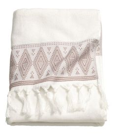 White. Bath towel in soft cotton terry with an embroidered pattern and tassels on short sides.