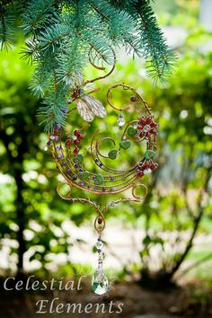 Sun Catcher adorned with dragonfly. Copper wire base shaped in a spiral, Beads create dynamic flowers designs, Crystals hang loosely,