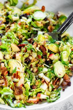 This shredded Brussels sprouts salad is loaded with so many delicious things Sweet chopped apples crispy bacon toasted hazelnuts and a sweet tangy apple vinaigrette It s paleo dairy-free with a option and perfect for a crowd or as a make ahead lunch Shredded Brussel Sprout Salad, Sprouts With Bacon, Brussels Sprouts Slaw Recipe, Brussels Salad Recipe, Shaved Brussel Sprouts, Salads For A Crowd, Food For A Crowd, Salads For Lunch, Clean Eating