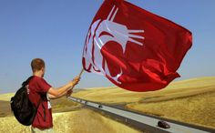 WSU student, A.J. Tullo, waves a flag at traffic headed south on Highway 195 at the Steptoe area, Saturday, Sept. 10, 2011. Tullo was one of about 70 students from Coug Guys and Gals which is comprised of students supporting the athletic department who were out showing some support for the WSU vs. UNLV football game at Martin Stadium on the WSU campus. (Christopher Anderson / Spokesman-Review)