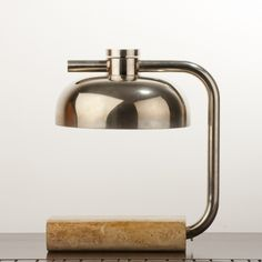 Desk lamp with thick travertine base and articulated nickeled metal shade. Circa 1940s.