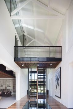 open stairwell. bridge. glass flooring above wine cellar. Jackson Clements Burrows Architects.