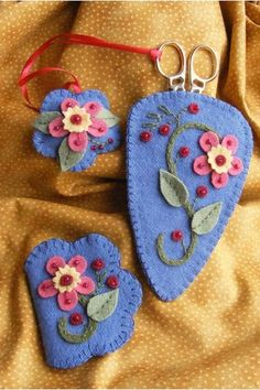 A pretty Wool Applique trio of needlework accessories to tuck into your sewing basket.  Coral blossoms are accented with sparkling red glass beads....all the colors are beautiful on the blue wool background.  Place a pair of our Victorian in the scissors case and put pins and needles in the petite folding needle keep.  The Emery scissor minder is so handy!