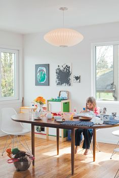 Daughter Zoë finds a cozy spot at the dining-room table, by Dux, seated on an Eames Molded Plastic chair and under a George Nelson Saucer lamp. Photo 3 of 14 in Cool Kid Hideouts by Paige Alexus from Z for Two