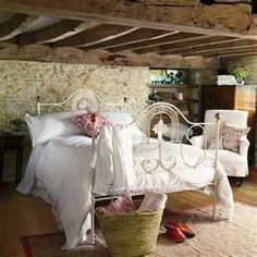 Cozy country bedroom ~ love the clean, white down comforter and wooden beams...