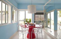 Na sala de jantar decorada pela arquiteta Andrea Murao,  o azul predomina nas paredes. A mesa vermelha faz o contraponto