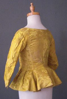 Girl's Chinese Silk  1770's jacket, of imperial yellow silk damask, the design with full blown flowers, their stems wound with leaves, with scoop neck and front opening with hooks and eyes, full skirt to the sides and back, the back with a central seam and a lower horizontal waist seam, simple sleeves with back seam, lined with same shade of yellow glazed linen.