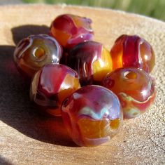 This set of lampwork glass beads was created on a deep buttery base glass. Then shards of silvered glass were melted onto the bead surface, partially fuming  the base and producing rich colors of plum, periwinkle and magenta.