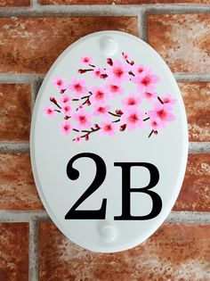 A range of pottery style house plaques feature prints of original artwork from our own sign artists. Hand cast in cultured marble these number plates are weatherproof outdoors. House Plaques, House Number Plaque, House Numbers, Floral Motif, Cherry Blossom, Original Artwork, Decorative Plates, Pottery, Prints