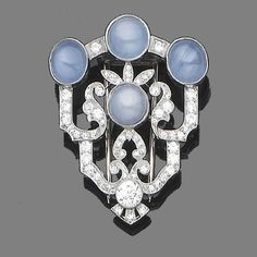 A star sapphire and diamond clip brooch  The millegrain-set cabochon star sapphires, within an openwork single and brilliant-cut diamond cartouche, diamonds approx. 1.20ct. total, length 4.2cm.