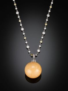 A work of art by Tiffany & Co., this magnificent necklace showcases a rare melo melo pearl, one of the most exceptional pearls in the world. Exhibiting an almost perfectly round shape and the highly desirable orange hue, this pearl is suspended from a platinum chain dotted with 6.50 carats of yellow and white diamonds and held securely by a diamond-studded box clasp.   An Asian passion with a long history of veneration, the extremely rare melo melo pearl is formed by the Melo Melo snail