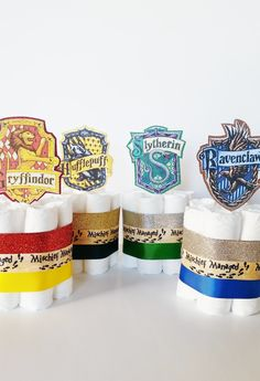 What better way to welcome the new muggle born with these Harry Potter themed diaper cake centerpieces! They will be a hit at your Hogwarts Baby Shower.  This set includes four (4) mini diaper cakes shown. Each diaper cakes has 7 size 2 diapers and is adorned with both glitter and grosgrain ribbon that coordinates with the Hufflepuff, Gryffindor, Ravenclaw, and Slytherin colors. Each diaper cake is topped with a handmade topper that represents the 4 house coat of arms. Each mini diaper cake…
