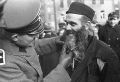 A Warsaw Jew is subjected to one of the first humiliation measures applied by the Germans: the cutting of the beard. In the absence of any other reaction, the victim is smiling. October 1939.