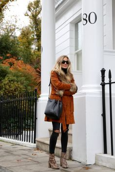 orange trench with fur collar and ends of sleeves/ripped jeans/snake skin boots