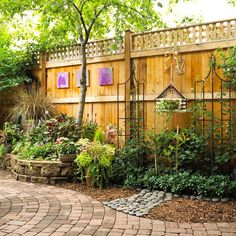 ✤ Landscaping Ideas for Privacy #8 – Fanciful Fence  Dress up a privacy barrier with accents.  In a mostly hardscape section of the garden, mixing materials heightens visual interest. Here, pavers combine with river rocks and shredded wood for a distinctive edge.  Garden ornaments, including an imaginative birdhouse planter and a series of bright purple paintings, adorn the fence.
