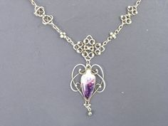 A Newlyn silver and enamel pendant, on ornate chain, the enamel in shades of purple with openwork surround. Sold by Gorringes.