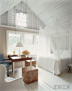 Lakehouse bedroom of Dara Caponigro w/ mosquito net canopy and white planked ceiling
