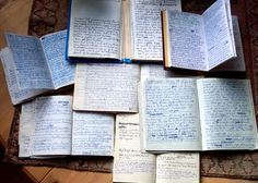 Pile of notebooks containing translations and completed pages from damaged grimoires.