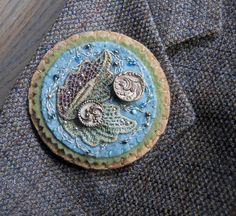 Wool felt brooch with hand dyed lace applique, antique buttons, embroidery, and beads. $50.00, via Etsy.