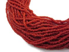 A vintage multi strand red coral seed beaded necklace. Has 30 strands of beads.  No marks. Some wear to the metal finish. Necklace is about 16.5