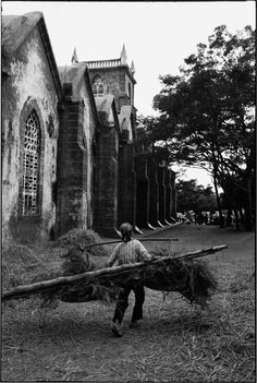 Region. 1995. A woman carrying a load next to a church built in 1869.
