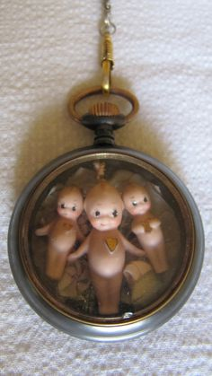 Vintage 1930s old gun metal pocket watch case containing 3 small bisque porcelain kewpies. The kewpies lay on a background of pale cream and green