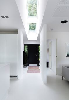 Bright, white and open entryway with skylight window - classic and sophisticated. A minimalistic look matches the clear lines.