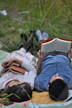 Lovers cuddled on a blanket in a meadow reading together........