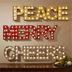 """Brighten spirits and show off your holiday style with these marquee signs. Available in """"Cheers"""", """"Merry"""" and """"Peace."""""""