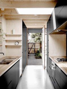 Une cuisine contemporaine en panneaux de bois avec son duo coloré noir et bois blond !