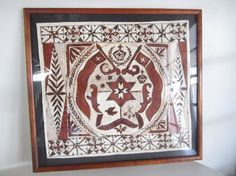 A framed Tongan Ngatu from the 1960's baring the Island of Tonga's crest on a handmade parchment from a mulberry tree using brown paint made from the koka tree. It is a very time consuming and magical process to make these tapa cloth that are often made for weddings or as special gifts. It was professionally framed.