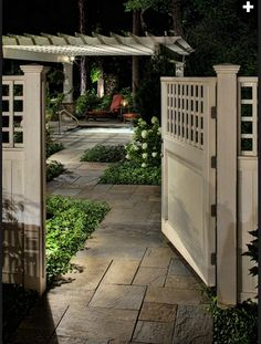 Romantic Backyard Getaway..  This smooth cedar entry gate opens to a luxurious pergola garden and spa that features accent and path lighting to create an intimate backyard setting. Design by Bob Hursthouse