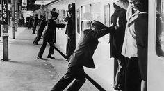 train platform workes, cramming commuters at rush hour.