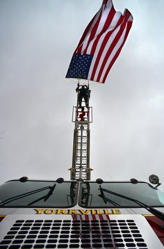 MARK DIORIO / OBSERVER-DISPATCH: Yorkville Fire Department Assistant Chief John Constas hangs a flag from a ladder truck parked by the Church of Our Lady of Lourdes during a funeral held for Utica Firefighter Matthew T. Benn, 29, Feb. 12, 2015 in Utica, N.Y. Benn was killed in a snowmobile accident Saturday, Feb. 7.