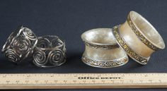 FOUR NAPKIN RINGS. INCLUDES TWO PAIR, ONE PAIR WITH A SPIRAL DESIGN, THE OTHER WITH A MARBLEIZED LOOK WITH RAISED TRIM. THIS SET IS CHIPPED.