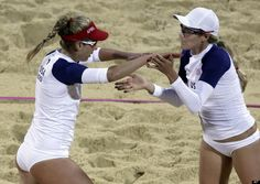 April Ross, left, and Jennifer Kessy of the United States react following a win in a beach volleyball match against Argentina at the 2012 Summer Olympics, Sunday, July 29, 2012, in London.