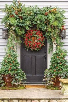 The arch above Rick Davis and Christopher Vazquez's front door is composed of evergreens, holly, English ivy, pine cones, and birch. The wreath showca. Christmas Front Doors, Christmas Porch, Outdoor Christmas, All Things Christmas, Vintage Christmas, Christmas Holidays, Christmas Wreaths, Christmas Crafts, Merry Christmas