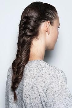 """Hairstylist Odile Gilbert, who created this style for Suno's spring show, calls this a """"herringbone braid."""" To achieve it, slick back hair and then part into three sections, crossing the lengths both over each other and underneath."""
