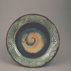 Cuzick Pottery.com - slip trailing, carving, fluid glazes create a ooak plate with the universe in the center