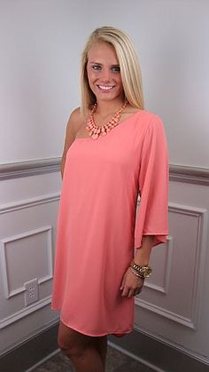 A little bit dressy, a little bit casual and fabulous all over! This whimsical peach dress features a single bell sleeve and sweeping hi-lo hemline. It is fully-lined and simply slips over your head. With our Princess K necklace and heels, it is perfect for an evening wedding. $46