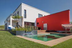Pultdach Klassik 268. Ein Haus im modernen Bauhausstil, das Wohnen und Arbeiten verbindet. Die beiden Baukörper werden dabei durch eine Wandscheibe getrennt, die auch die Außenbereiche gliedert.  Highlights sind der Lichtausschnitt über der Küche, der Schwimmteich sowie der Grillplatz im Garten. 268,18 m² Gesamtwohnfläche