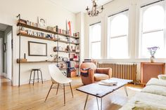industrial pipe shelving Living Room Scandinavian with arched windows bookshelves brown armchair chandelier open shelves radiator