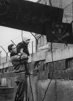 A West German man lifts his son to give him a view of the other side of the Berlin Wall in January 1961.