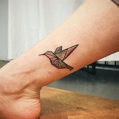 the hummingbird tattoo on the lower leg is made in a dot work technique