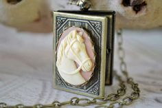 Capturing a look of timeless elegance, this book style locket features a resin horse cameo framed in brass. Suspended from a scrollwork