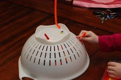 Using a pincer grasp, thread pipe cleaners through colander. And to add a sensory component, you could vary the texture of the pipe cleaners! :)