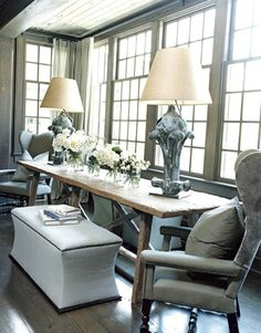 Great long rustic trestle table and curved ottoman benches in a windowed alcove