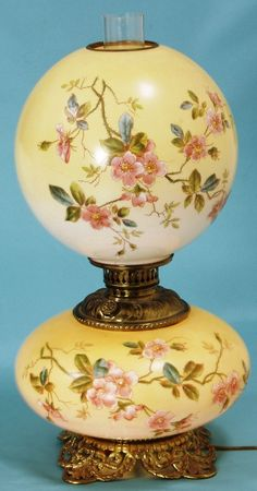 Circa 1900 21-inch tall Gone With the Wind lamp.  Both the top globe and base have a yellow case glass background decorated with cherry blossoms.