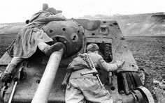 Russian soldiers using the wreck of an SU-85 for cover whilst scouting for the enemy, Ukraine 1944.